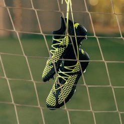 Le scarpe Puma future appese alla rete da calcio